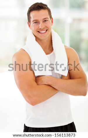 smiling young man at the gym with arms folded after exercise - stock photo
