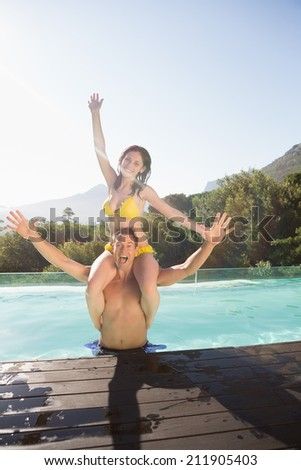 Smiling young man carrying cheerful woman by swimming pool on a sunny day - stock photo