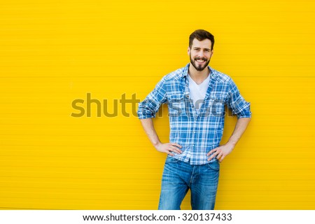 Smiling young man casual dressed standing against yellow background, showing one side - stock photo