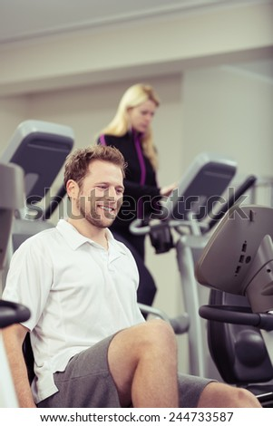 Smiling young man exercising on the equipment at the gym with a young woman working out behind in a healthy lifestyle concept - stock photo