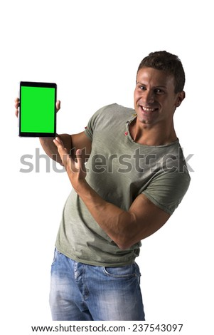 Smiling young man holding and showing ebook reader, standing isolated on white background - stock photo