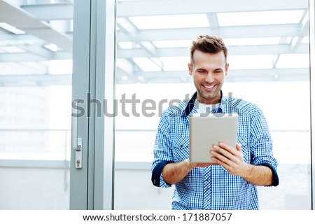 Smiling young man holding and using a digital tablet - stock photo