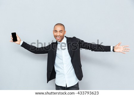 Smiling young man holding his smart phone isolated on grey background - stock photo