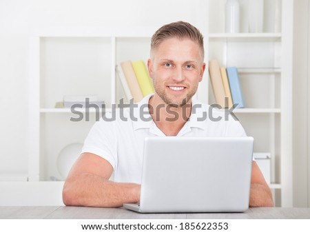 Smiling young man in a short sleeved shirt sitting working at home on a laptop in a home office - stock photo