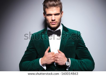 smiling young man in an elegant velvet suit with bow tie is looking at the camera on a gray background - stock photo