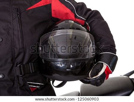 Smiling young man in protective gear holding a helmet under his arm with his red motorbike on a white studio background - stock photo