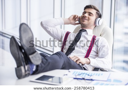 Smiling young man in suit is listening music in headphone in office. - stock photo
