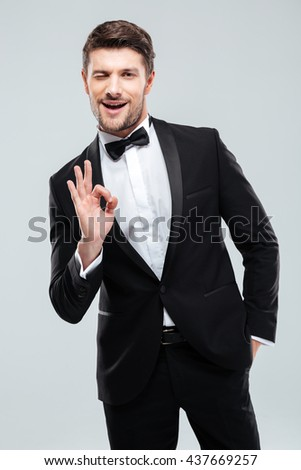 Smiling young man in tuxedo with bowtie winking and showing ok sign - stock photo