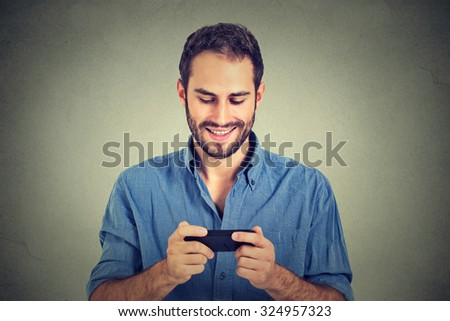 Smiling young man looking at his smart phone while text messaging or watching video, movie, pictures isolated on gray wall background. Positive face expression  - stock photo