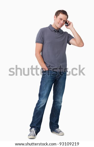 Smiling young man on his cellphone against a white background - stock photo