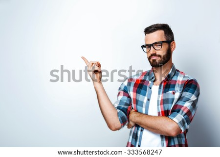 Smiling young man on white background. Stylish man wearing glasses, looking at camera and pointing at bland wall - stock photo