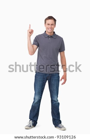 Smiling young man pointing up against a white background - stock photo