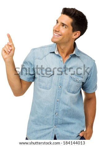 Smiling young man pointing upwards against white background. Vertical shot. - stock photo