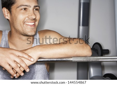 Smiling young man resting on barbell after workout at gym - stock photo