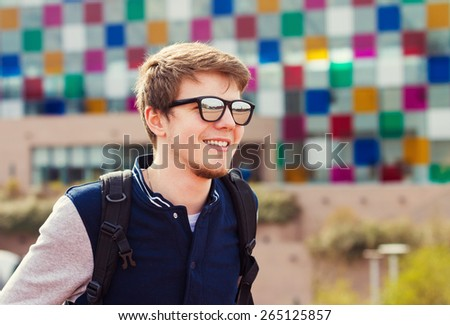 Smiling young man sitting in a city park.Young smiling student  outdoors Life style.Park - stock photo