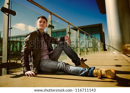 Smiling young man sitting in street - stock photo