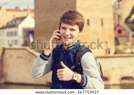 Smiling young man talking on mobile phone in a city with thumb up .Young smiling student  outdoors talking on cell smart phone.Life style.City - stock photo