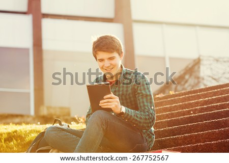 Smiling young man taping on tablet in a city on stair .Young smiling student  outdoors  with tablet.Life style.City - stock photo