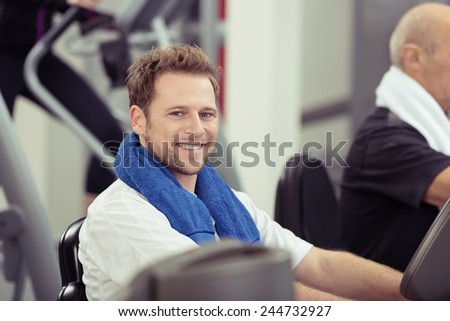 Smiling young man training at the gym working out on the equipment with a towel around his neck, in a health and fitness concept - stock photo
