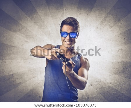 Smiling young man using a video-game controller - stock photo