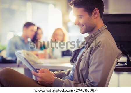 Smiling young man using digital tablet in the office - stock photo