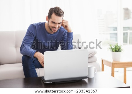 Smiling young man using his laptop at home in the living room - stock photo