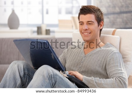 Smiling young man using laptop computer sitting in armchair in living room, smiling.? - stock photo