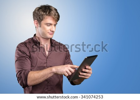 Smiling young man using tablet computer - stock photo