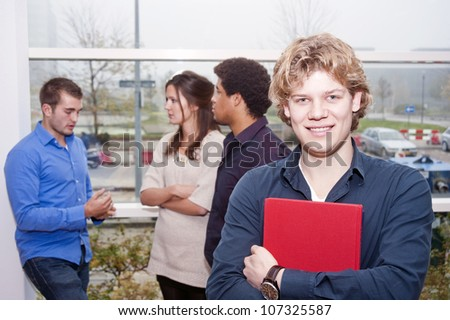 Smiling young man walking between lectures on a college campus with other students talking in the background - stock photo