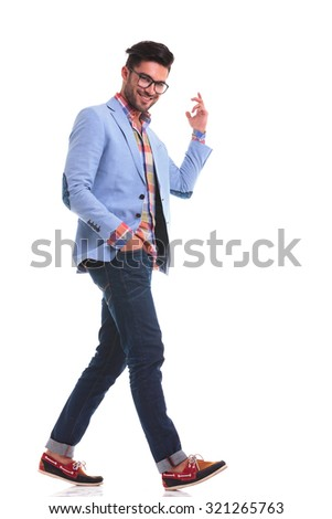 Smiling young man walking on isolated background while holding his hand in pocket. - stock photo