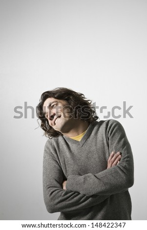 Smiling young man with arms crossed standing against gray background - stock photo