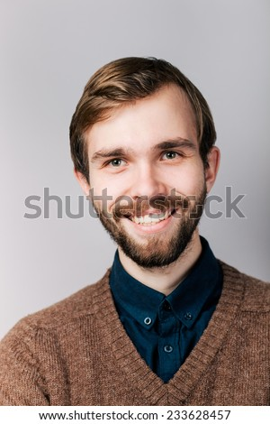 smiling young man with beard in brown sweater - stock photo