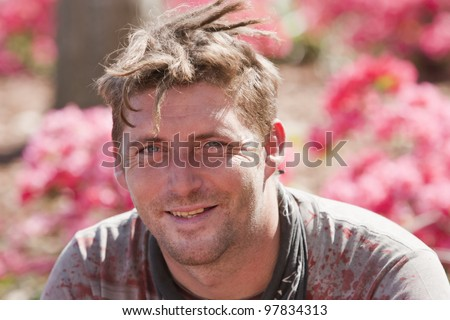 Smiling young man with dreadlocks. Shot outside during the daytime - stock photo