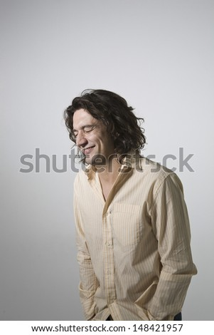 Smiling young man with eyes closed standing against gray background - stock photo
