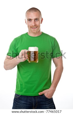 Smiling young man with glass of frothy beer; isolated on white background. - stock photo