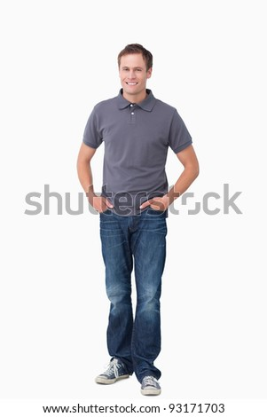 Smiling young man with hands in his pockets against a white background - stock photo