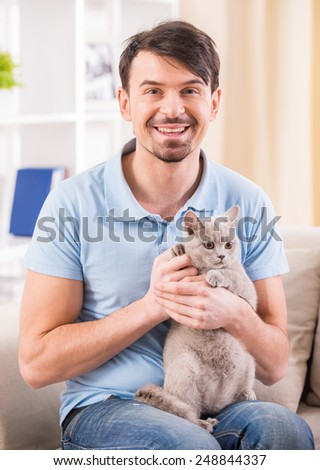 Smiling young man with his cute cat on the couch at home. - stock photo