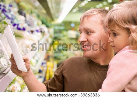Smiling young man with little girl buy parsley in supermarket - stock photo