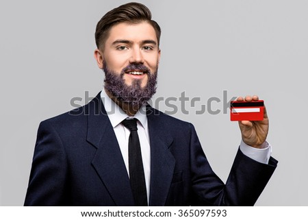 Smiling young man, with violet beard, wearing in dark blue suit and tie, posing with red credit card in his hands, waist up - stock photo