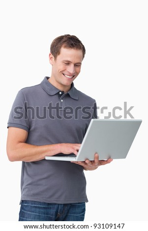 Smiling young man working on laptop against a white background - stock photo