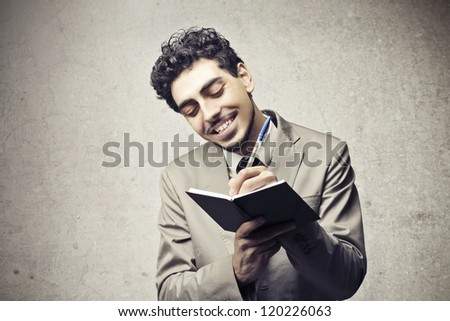Smiling young man writing on an agenda - stock photo