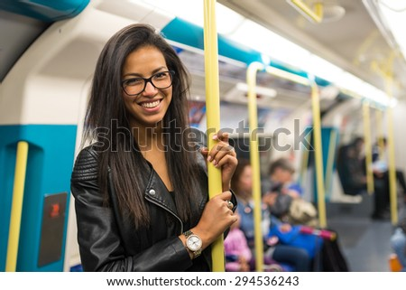 Smiling young mixed race businesswoman portrait inside underground wagon in London. - stock photo