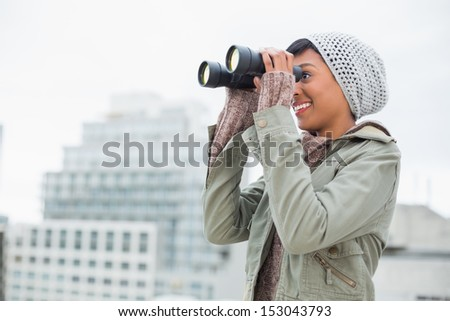 Smiling young model in winter clothes watching with binoculars outside on a cloudy day - stock photo