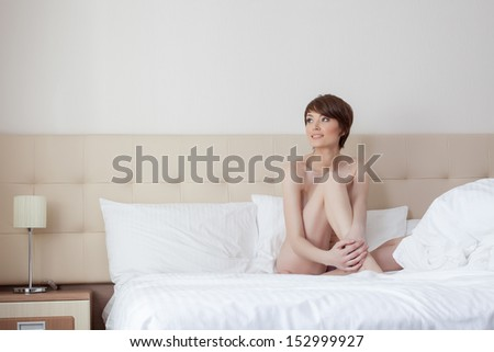 Smiling young model posing naked on hotel's bed - stock photo