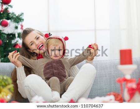 Smiling young mother and baby having fun time on Christmas - stock photo