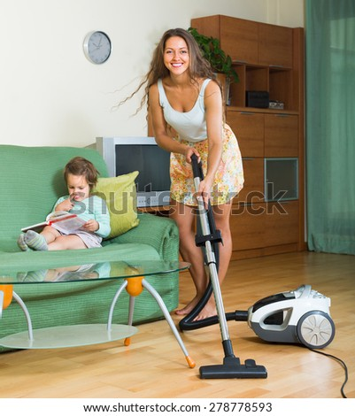 Smiling young mother and daughter chores with vacuum cleaner in home. Focus on woman - stock photo
