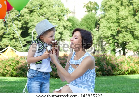 Smiling young mother and little son eating ice-creams together in a summer park - stock photo