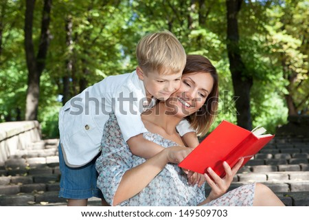 Smiling young mother and son spending time together in a summer park - stock photo