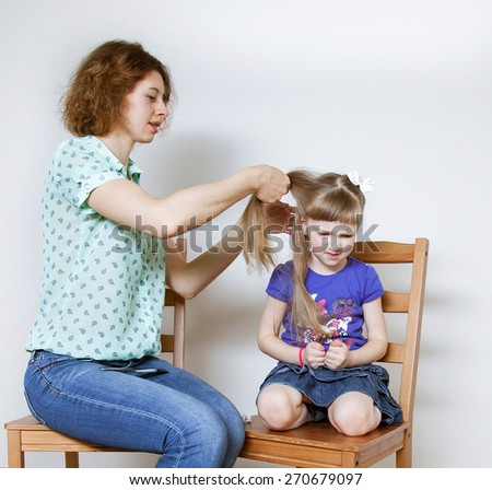 Smiling young mother braiding hair her little daughter, neutral background - stock photo