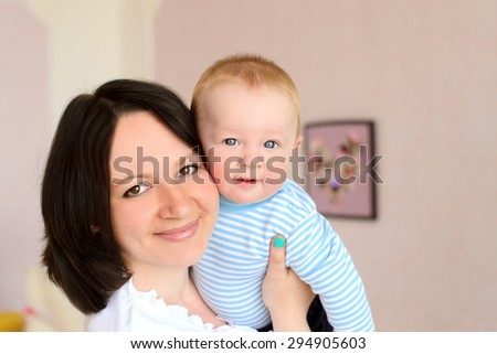 smiling young mother holding cute baby son indoors - stock photo